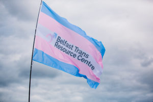 A large trans flag emblazoned with the Belfast Trans Resource Centre logo, free flying on a pole