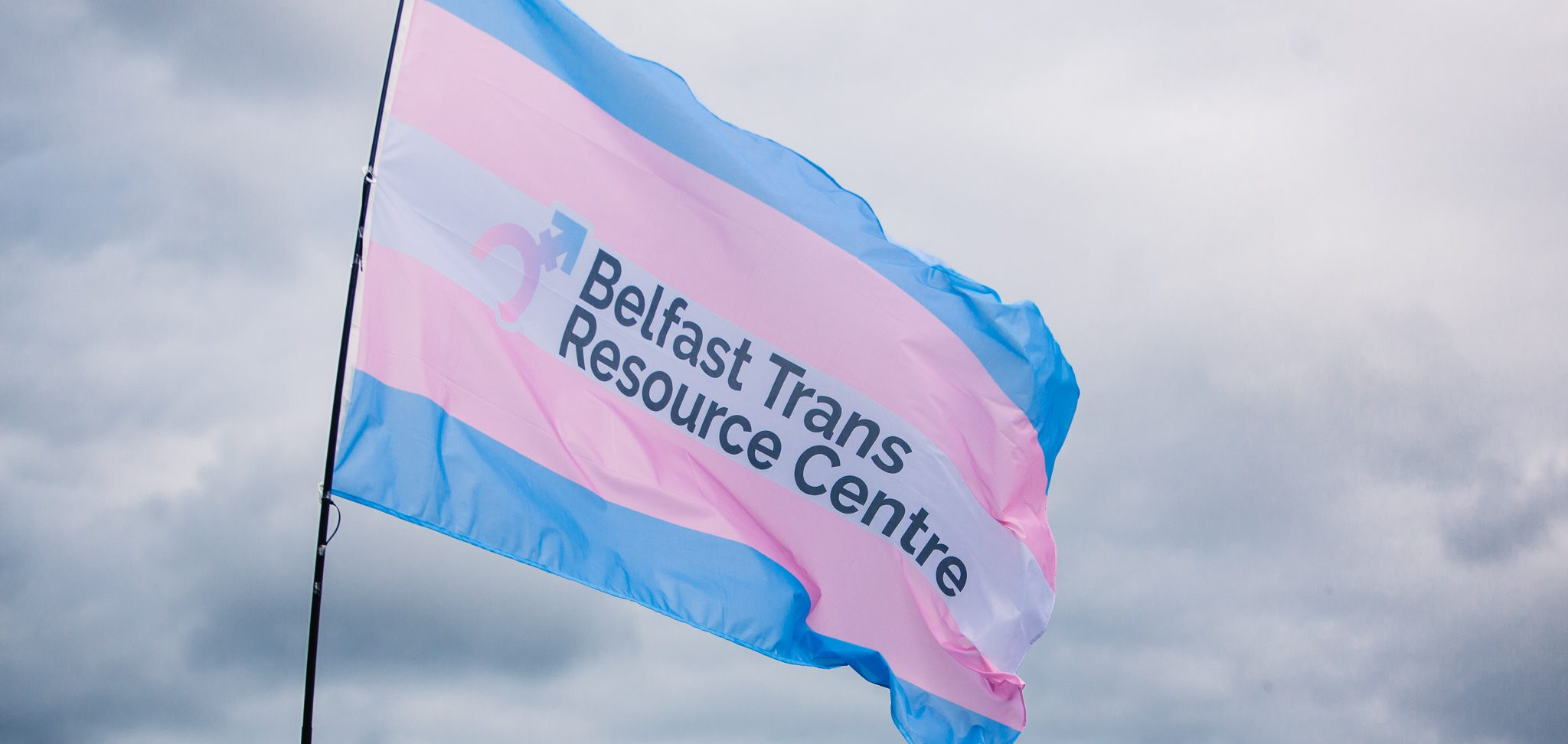 A large flying trans flag emblazoned with the Belfast Trans Resource Centre logo.